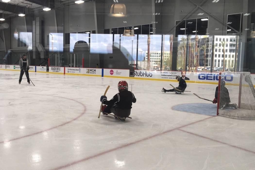 John Coogan, left, practices with sled hockey players at City National Arena. Courtesy: Gina Kielb/Jake Kielb Foundation.