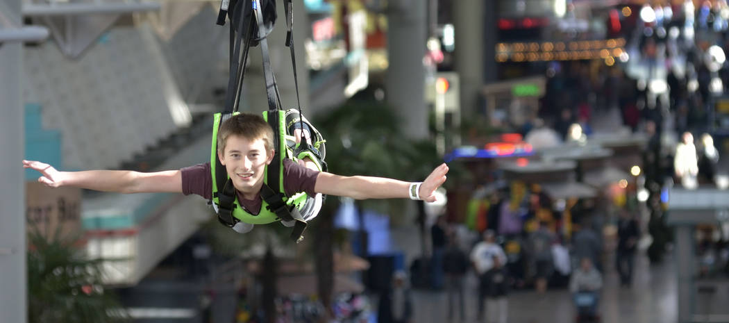 Blake Anderson, son of Clark County firefighter Keith Anderson, rides the zip line during the SlotZilla Charity Challenge of 2015 at the Fremont Street Experience in downtown Las Vegas on Thursday ...