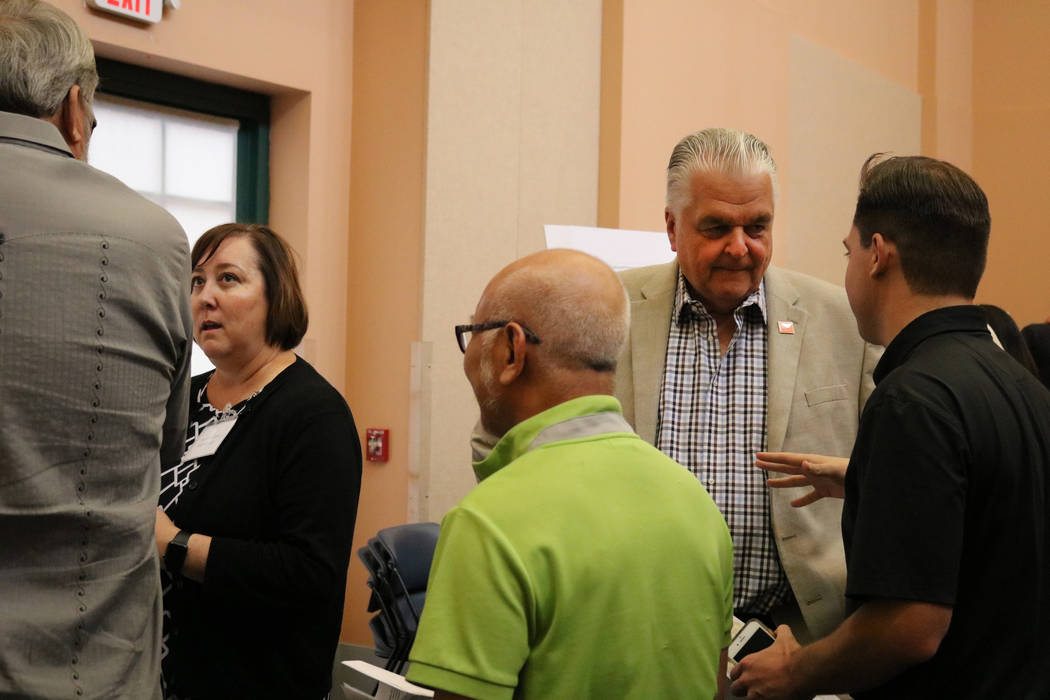 Marci Henson, left, and Clark County Commissioner Steve Sisolak, right, speak to members of the public at an open house at the Clark County Library in Las Vegas, Tuesday, June 5, 2018. A crowd fil ...