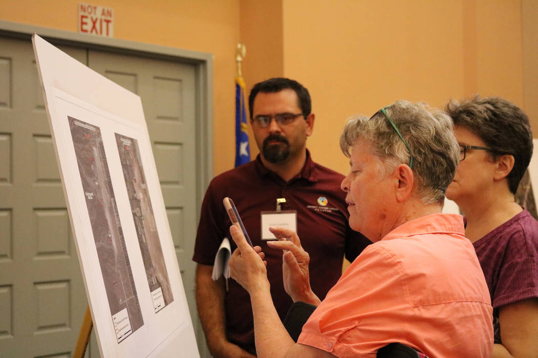 Jane Smith of Las Vegas looks over a poster board while Clark County biologist Scott Cambrin explains a proposed public lands bill at the Clark County Library in Las Vegas, Tuesday, June 5, 2018. ...