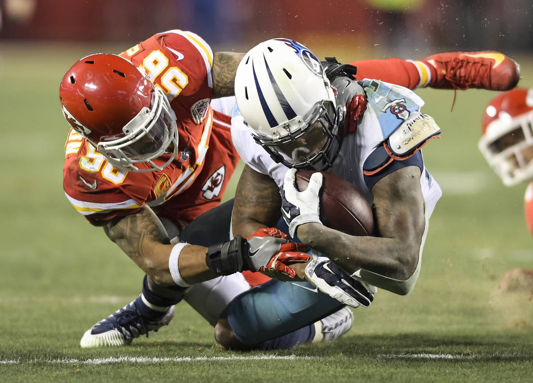 Tennessee Titans running back Derrick Henry (22) is tackled by Kansas City Chiefs inside linebacker Derrick Johnson (56) during the second half of an NFL wild-card playoff game in Kansas City, Mo. ...