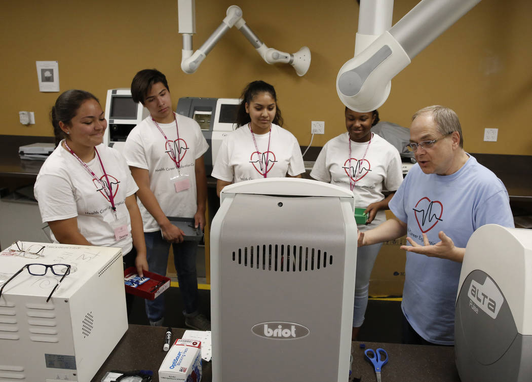 Clark County High School students, Deserae Olsen, left, Cristobal Luna, Maryanna Muñoz, Kaelyn Yarbrough, second right, listen as Scott Helkaa, right, program director, Ophthalmic Technology ...