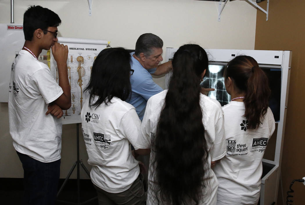 James Godin, chair, Dental Diagnostic and Rehab Service at College of Southern Nevada, demonstrates how to read a chest CT scan to Clark County High School students, including Ameya Singh, left, d ...
