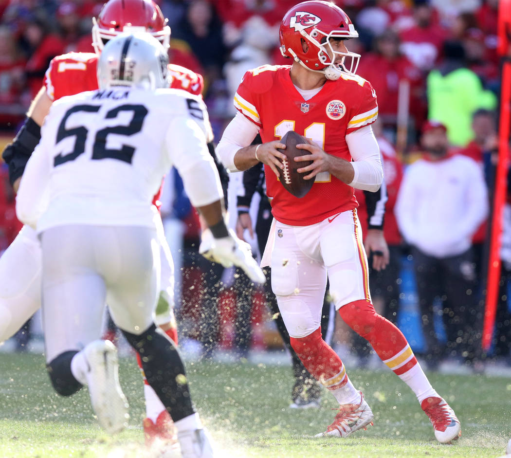 Kansas City Chiefs quarterback Alex Smith (11) drops back to throw as Oakland Raiders defensive end Khalil Mack (52) pursues him during the first half of a NFL game in Kansas City, Mo., Sunday, De ...