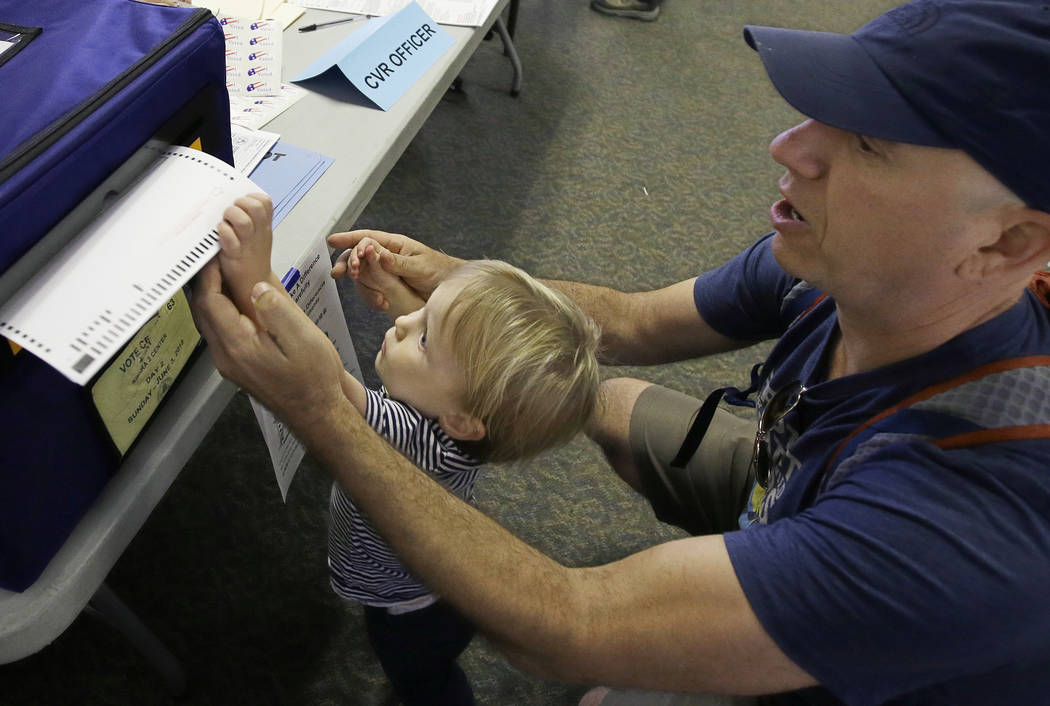 Christopher PapouchiIs gets help casting his ballot from his son, Nicholas, 2, Tuesday, June 5, 2018, in Sacramento, Calif. Voters are casting ballots in California's primary election, setting the ...