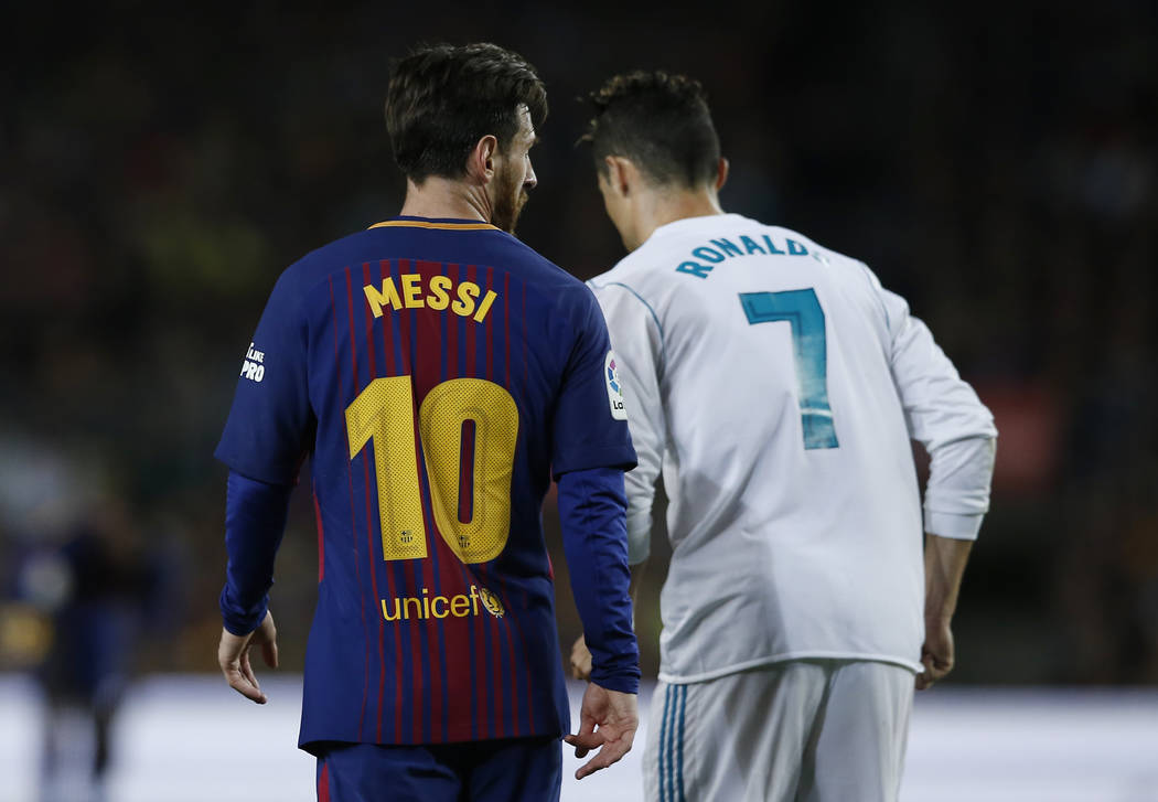 Barcelona's Lionel Messi, left and Real Madrid's Cristiano Ronaldo walk back to take positions during a Spanish La Liga soccer match between Barcelona and Real Madrid, dubbed 'el clasico', at the ...