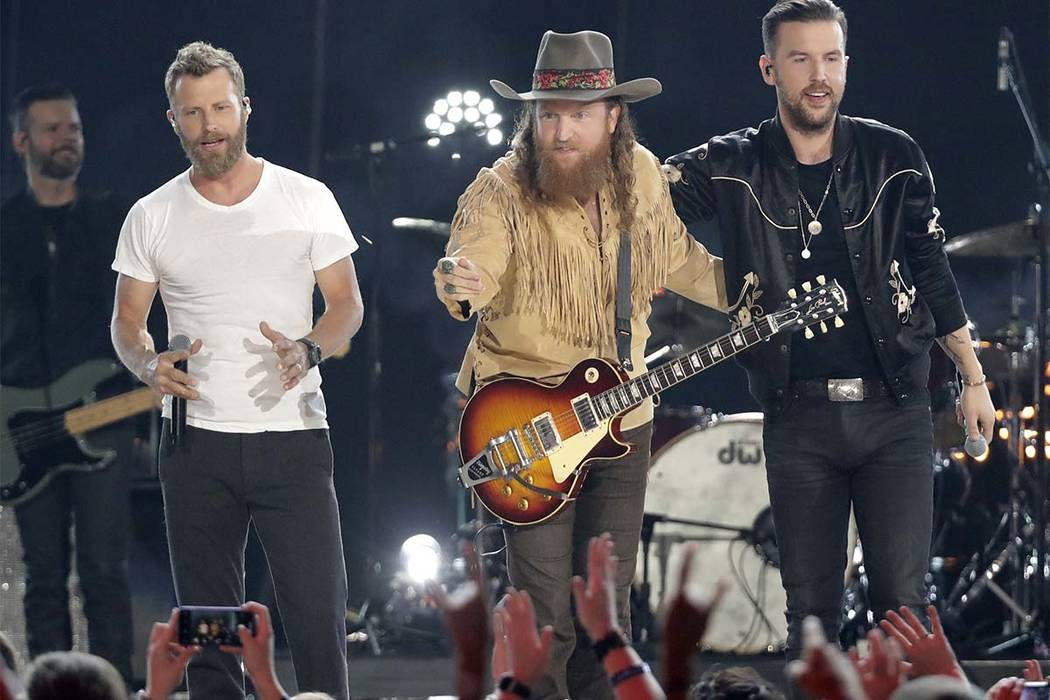 "Dierks Bentley, from left, John Osborne and T.J. Osborne, of Brothers Osborne, perform ""Burning Man"" at the CMT Music Awards at the Bridgestone Arena on Wednesday, June 6, 2018, in Nashv ..."