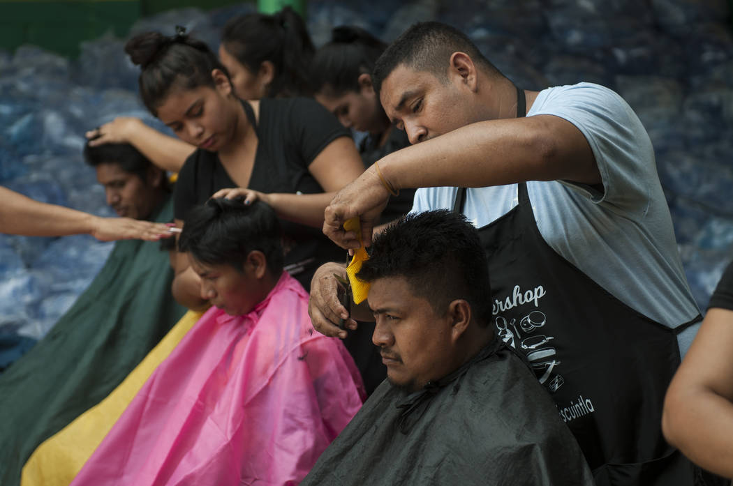 Student stylists trim the singed hair of residents who were burned during the powerful Volcan del Fuego or Volcano of Fire eruption, at a shelter near Escuintla, Guatemala, Wednesday, June 6, 2018 ...