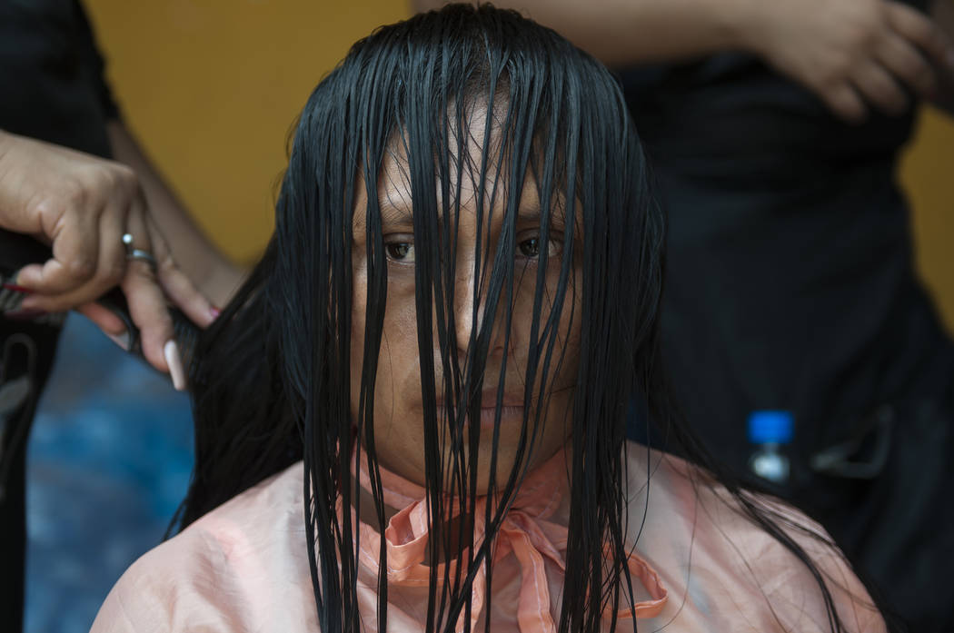 A displaced woman sits still as a student stylist trims her hair that was singed during the powerful Volcan del Fuego or Volcano of Fire eruption, at a shelter near Escuintla, Guatemala, Wednesday ...