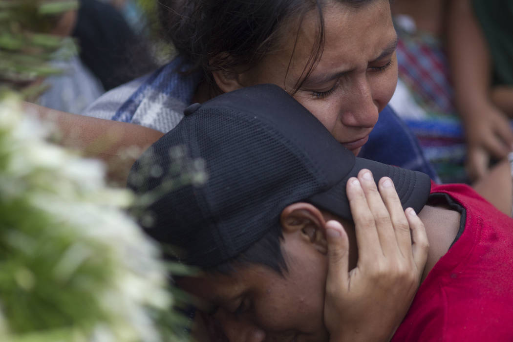 Kimberly Sofia Gonzalez consoles her husband Milton Rivas during the burial of his brother Erick Rivas, 20, who died in the hospital after suffering burns from the eruption of the Volcan de Fuego, ...