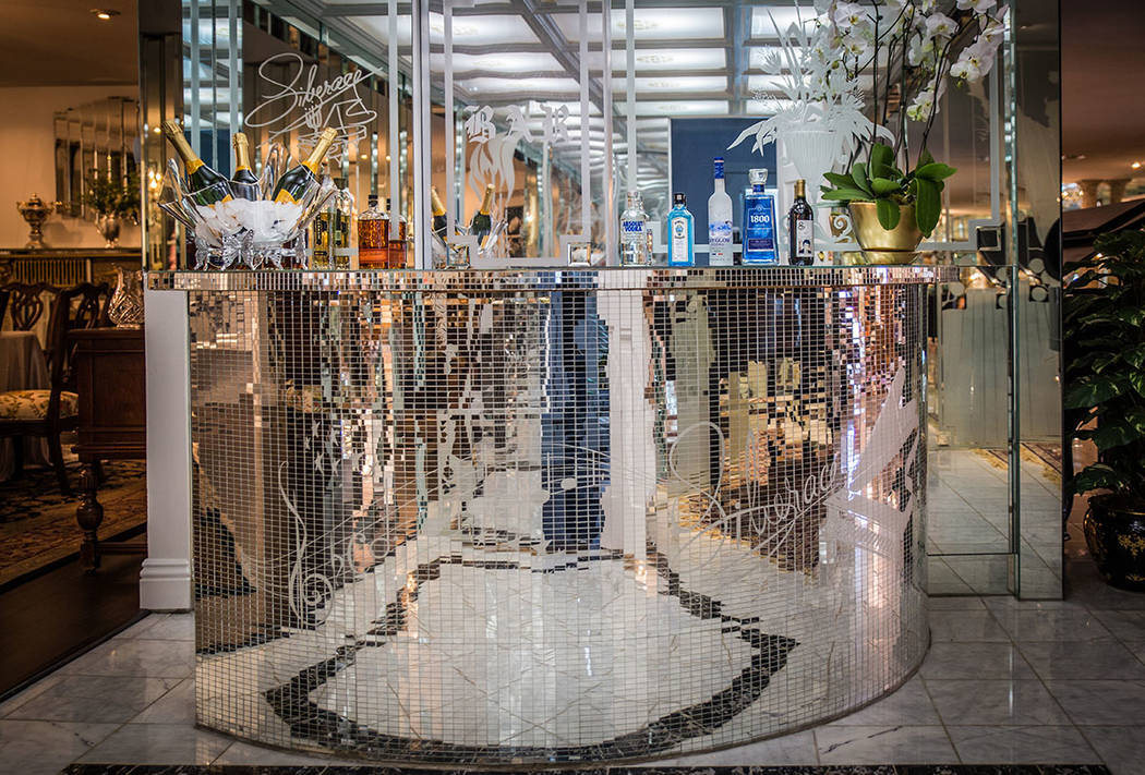 A decorative mirrored bar with etchings of Liberace's name and music notes are near a formal dining room. (Tonya Harvey Real Estate Millions)