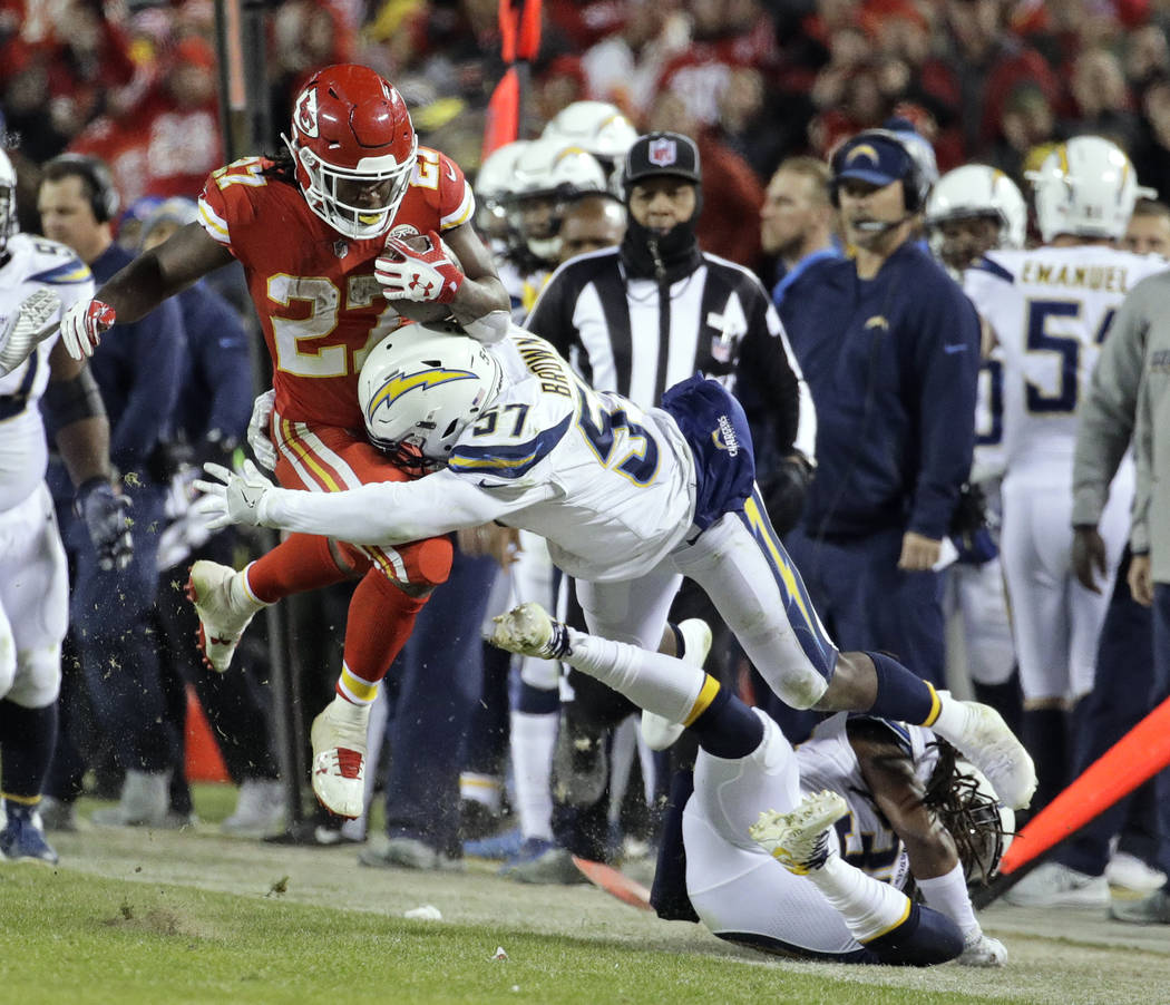 Kansas City Chiefs running back Kareem Hunt (27) is tackled by Los Angeles Chargers linebacker Jatavis Brown (57) and safety Tre Boston (33) during the second half of an NFL football game in Kansa ...
