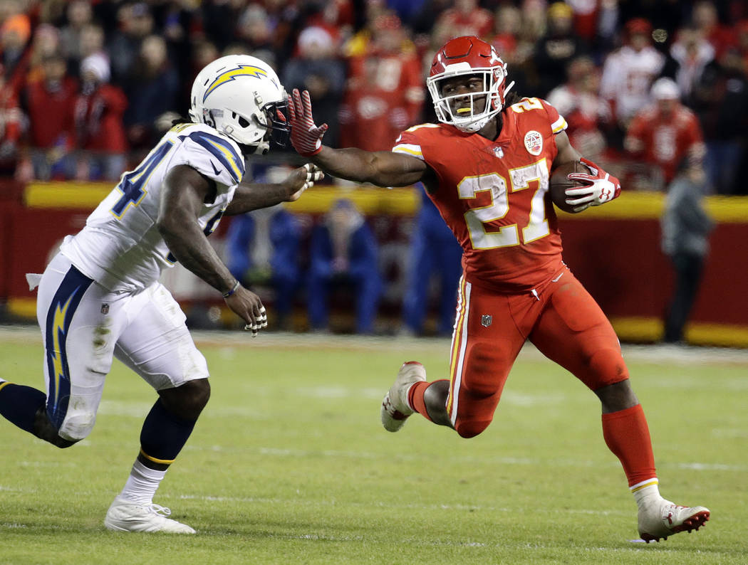 FILE - In this Dec. 16, 2017, file photo, Kansas City Chiefs running back Kareem Hunt (27) runs away from Los Angeles Chargers linebacker Melvin Ingram (54) during the second half of an NFL footba ...