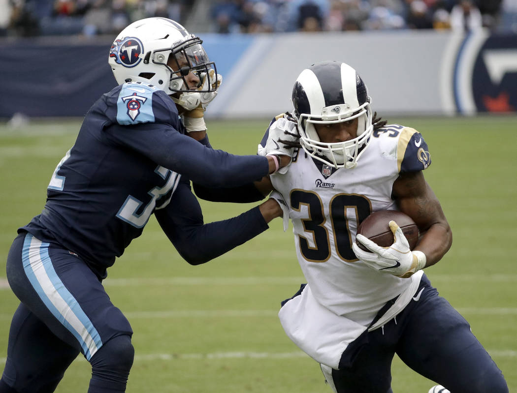 Los Angeles Rams running back Todd Gurley (30) tries to push away from Tennessee Titans free safety Kevin Byard, left, in the second half of an NFL football game Sunday, Dec. 24, 2017, in Nashvill ...