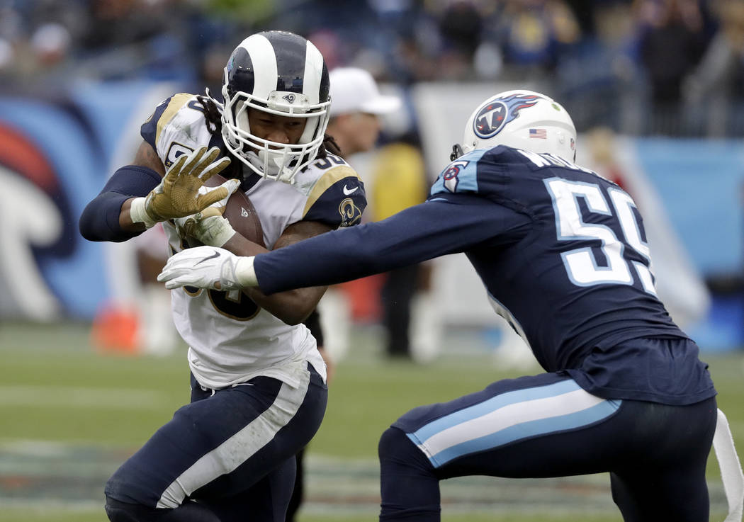 Los Angeles Rams running back Todd Gurley (30) runs against Tennessee Titans inside linebacker Wesley Woodyard (59) in the second half of an NFL football game Sunday, Dec. 24, 2017, in Nashville, ...