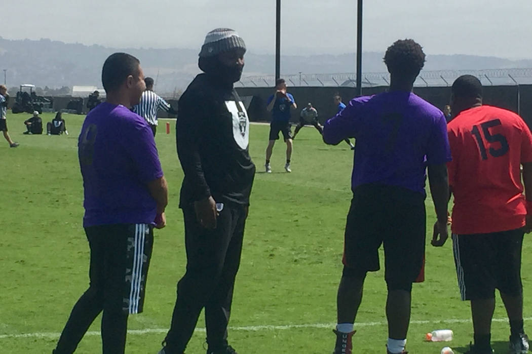 Raiders running back Marshawn Lynch speaks to a prep football player at a 7-on-7 passing league tournament that the franchise hosted at its headquarters in Alameda, Calif., on June 7, 2018. (Micha ...
