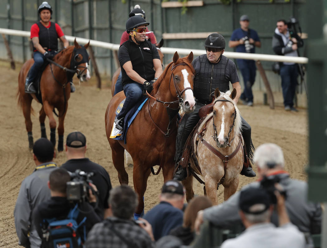 Triple Crown hopeful Justify is led off the track after a workout at Belmont Park, Thursday, June 7, 2018, in Elmont, N.Y. Justify will attempt to become the 13th Triple Crown winner when he races ...