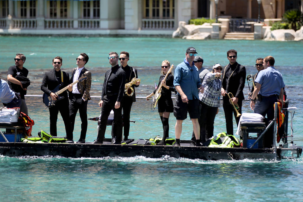 Frontman Brendon Urie, third from left, and members of the Las Vegas rock band Panic! at the Disco take a boat ride to the stage before performing at the Fountains at Bellagio ahead of the Vegas G ...