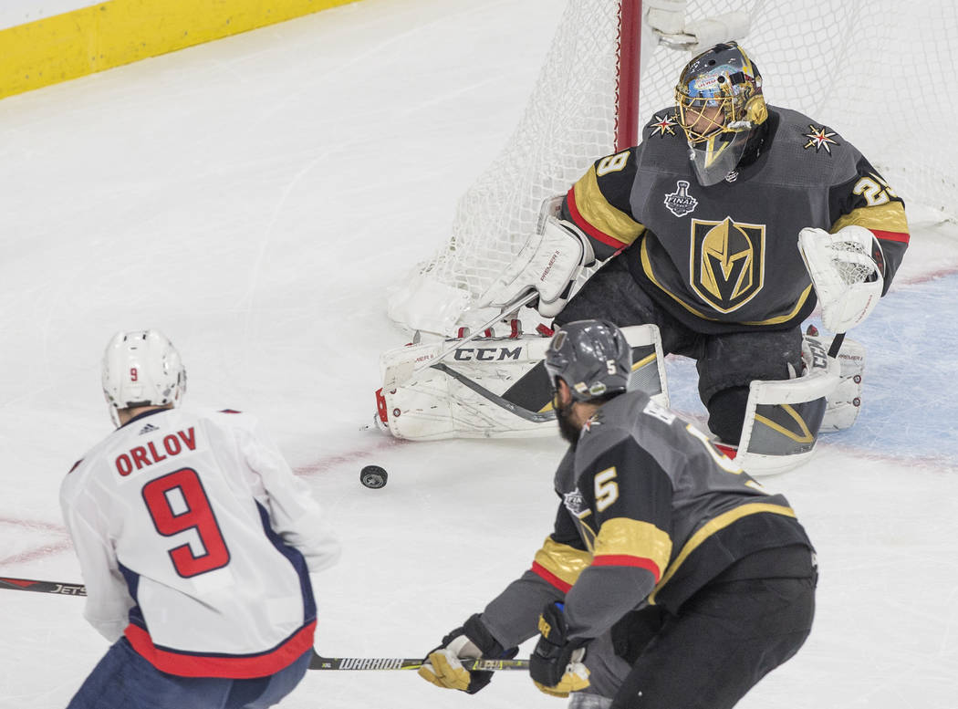 Golden Knights goaltender Marc-Andre Fleury (29) makes a save against Capitals defenseman Dmitry Orlov (9) in the first period during Game 5 of the NHL Stanley Cup Final on Thursday, June 7, 2018, ...