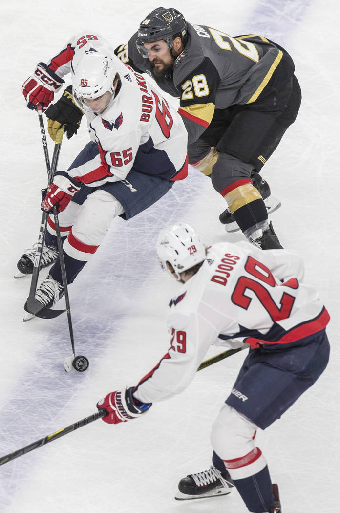 Golden Knights left wing William Carrier (28) fights for the puck with Capitals left wing Andre Burakovsky (65) in the first period during Game 5 of the NHL Stanley Cup Final on Thursday, June 7, ...