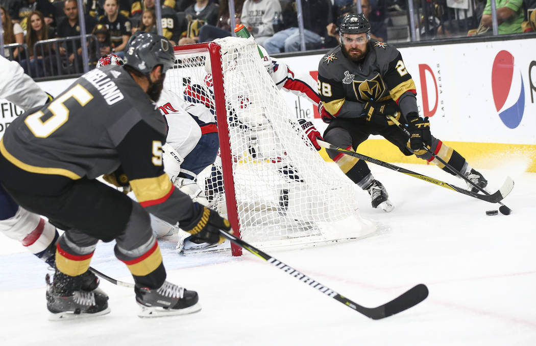 Golden Knights left wing William Carrier (28) and Golden Knights defenseman Deryk Engelland (5) moves the puck around the net during the first period of Game 5 of the Stanley Cup Final against the ...