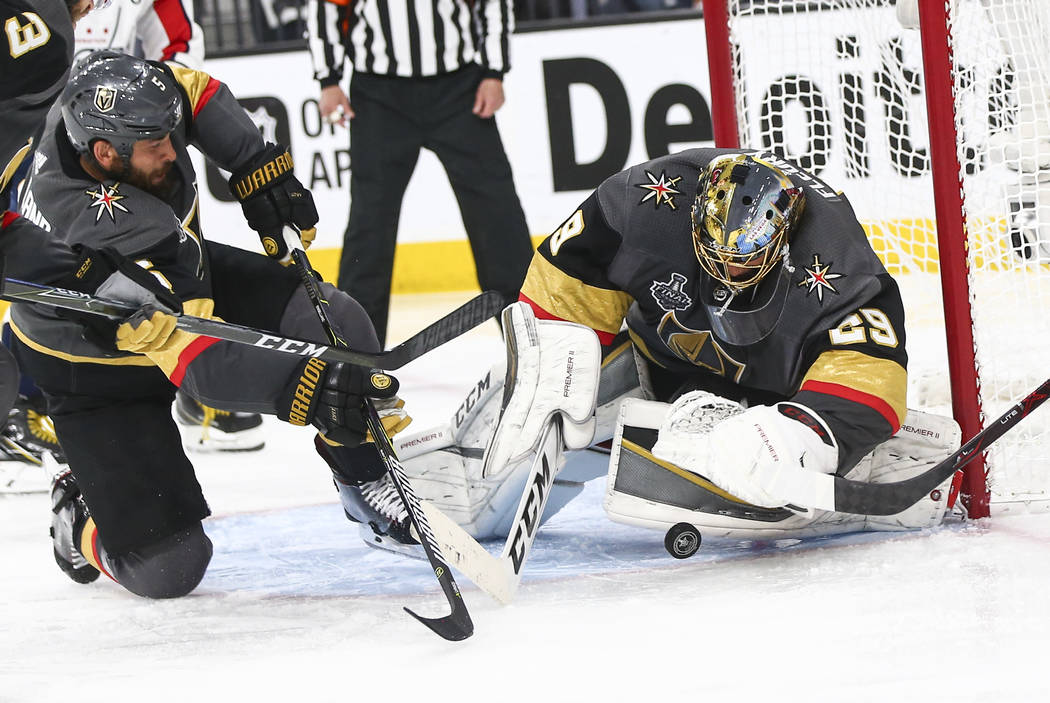 Golden Knights goaltender Marc-Andre Fleury (29) blocks a shot from Washington Capitals center Evgeny Kuznetsov, not pictured, in front of defenseman Deryk Engelland (5) during the second period o ...