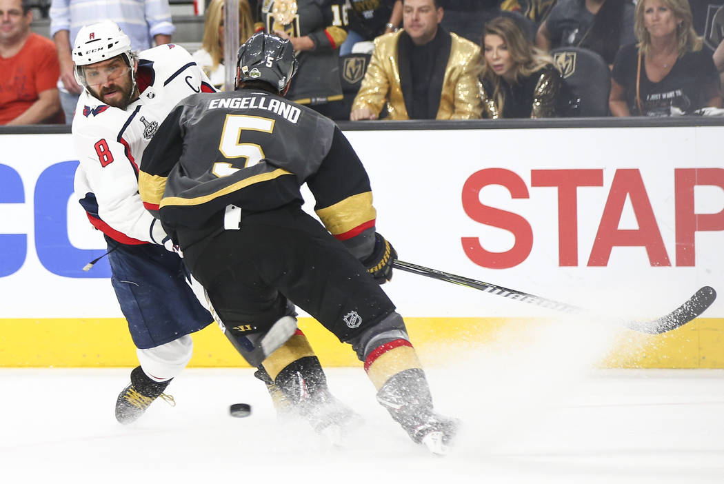Washington Capitals left wing Alex Ovechkin (8) sends the puck past Golden Knights defenseman Deryk Engelland (5) during the second period of Game 5 of the Stanley Cup Final at T-Mobile Arena in L ...