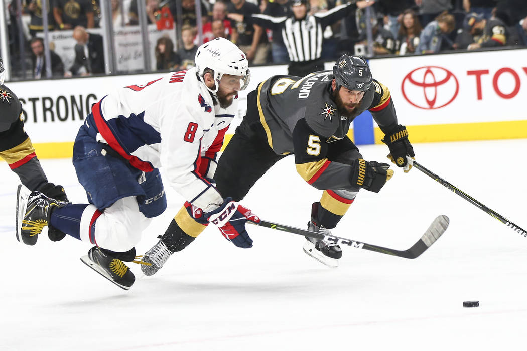 Washington Capitals left wing Alex Ovechkin (8) and Golden Knights defenseman Deryk Engelland (5) chase after the puck during the second period of Game 5 of the Stanley Cup Final at T-Mobile Arena ...