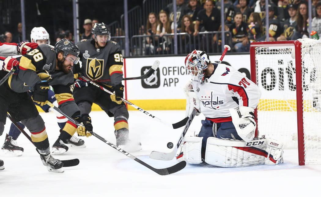 Washington Capitals goaltender Braden Holtby (70) defends as Golden Knights left wing William Carrier (28) and Tomas Nosek (92) try to get in the puck during the first period of Game 5 of the Stan ...