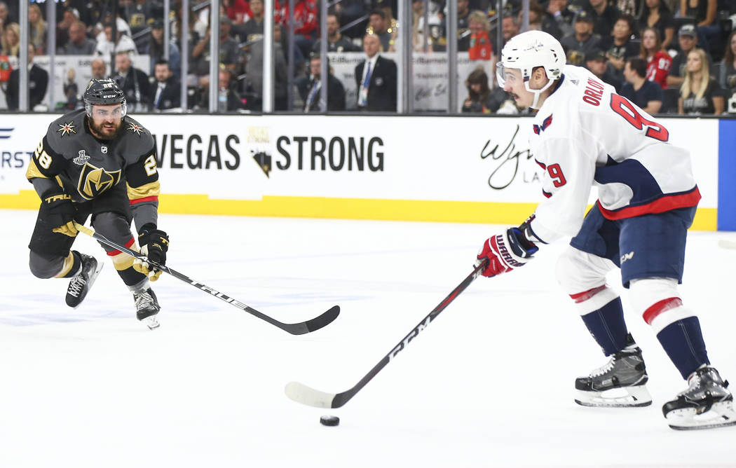Washington Capitals defenseman Dmitry Orlov (9) moves the puck as Golden Knights left wing William Carrier (28) defends during the first period of Game 5 of the Stanley Cup Final at T-Mobile Arena ...
