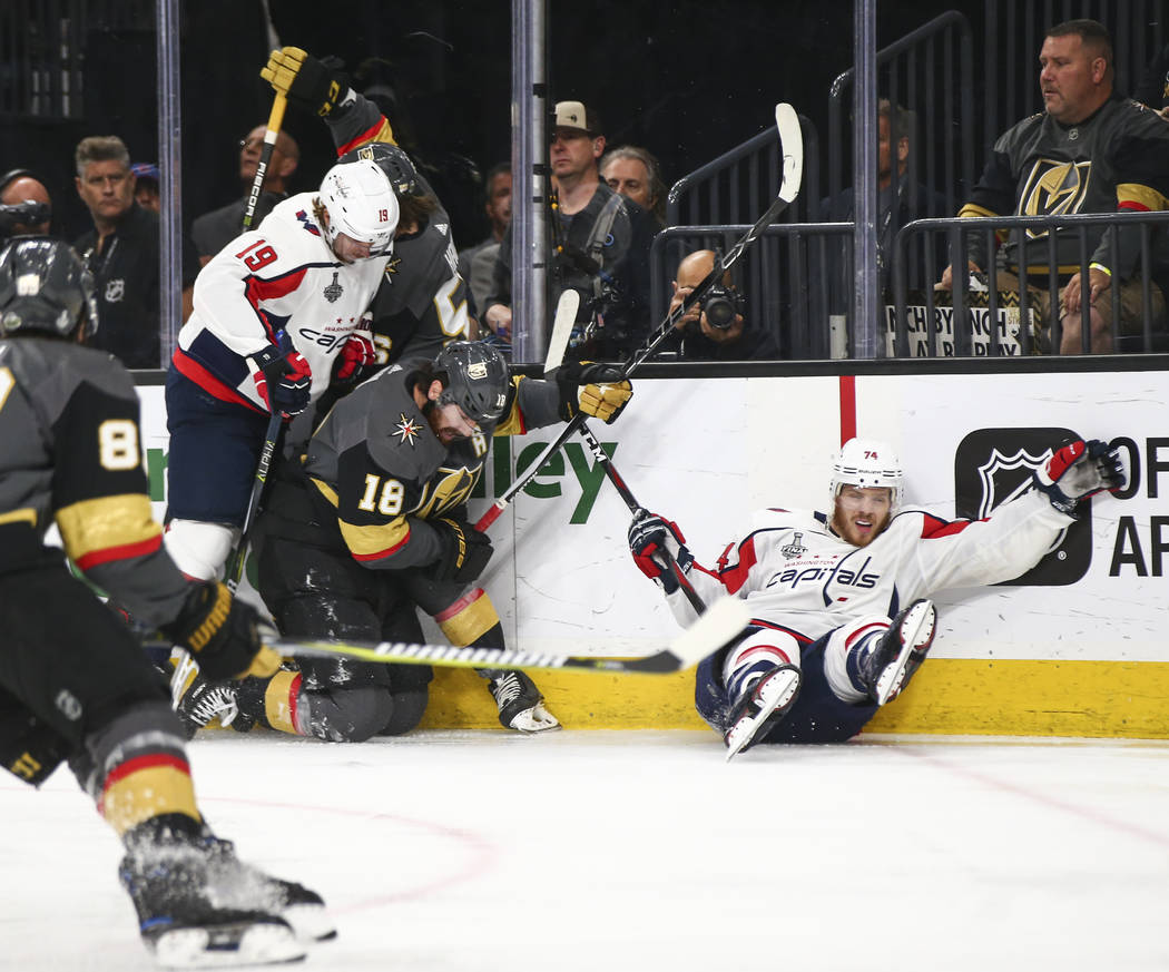 Washington Capitals defenseman John Carlson (74) gets tripped up in front of Golden Knights left wing James Neal (18) and Washington Capitals center Nicklas Backstrom (19) during the first period ...