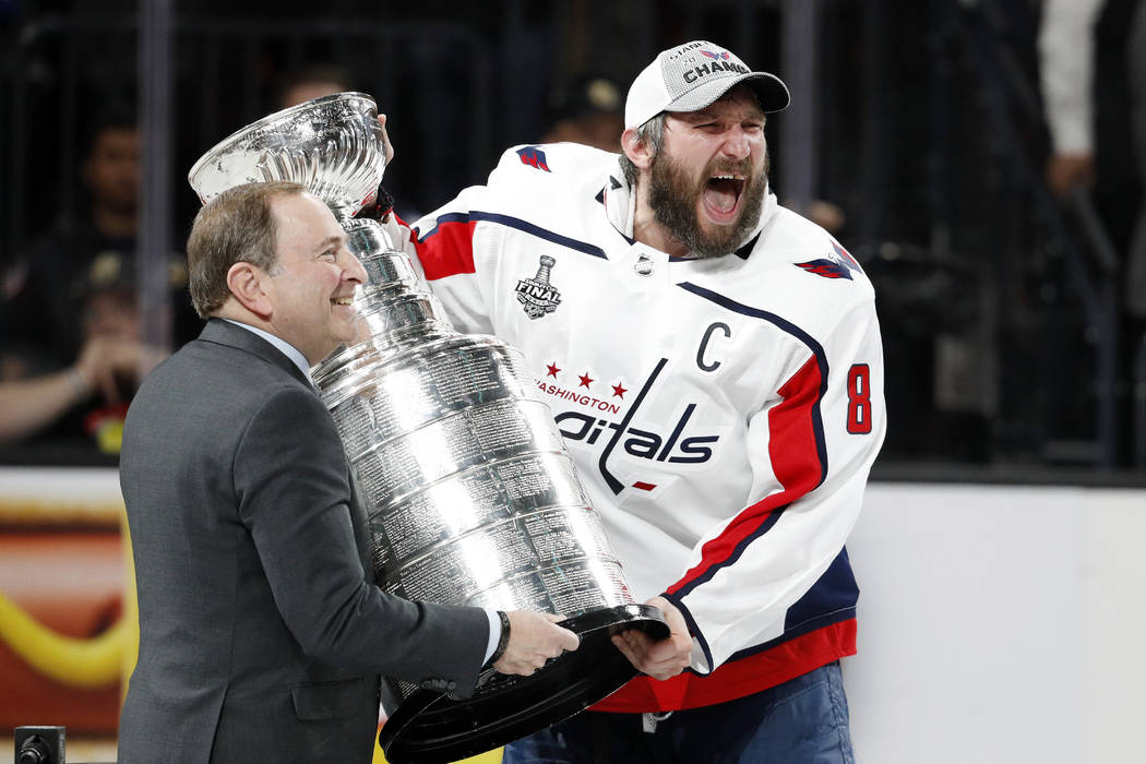 Washington Capitals left wing Alex Ovechkin, right, of Russia, celebrates as he takes the Stanley Cup from NHL commissioner Gary Bettman after the Capitals defeated the Golden Knights 4-3 in Game ...