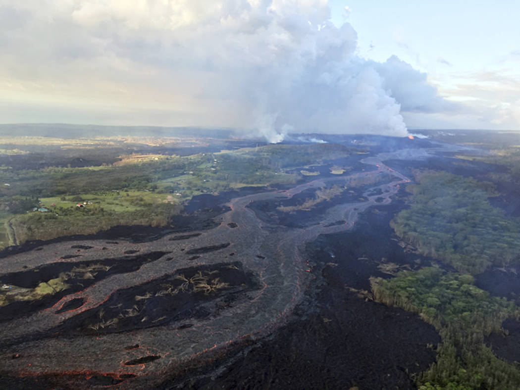 This Wednesday, June 6, 2018 photo from the U.S. Geological Survey shows Kilauea's lower East Rift Zone, showing continued fountaining of a fissure and the lava flow channel fed by it near the tow ...