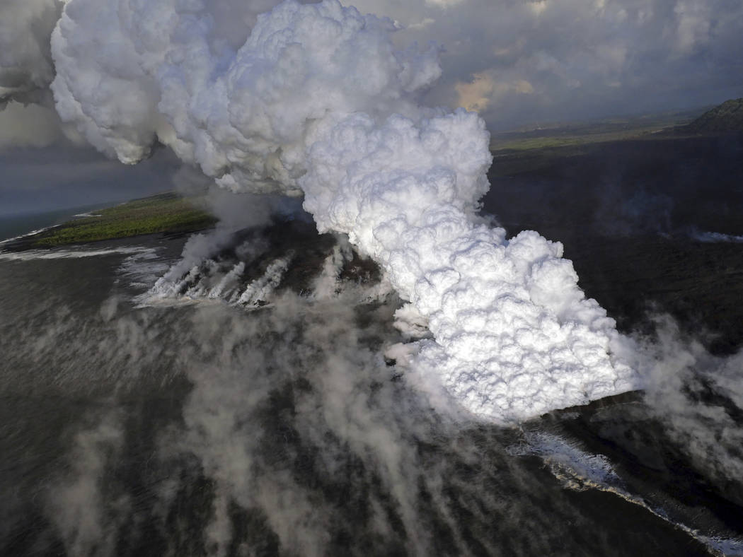 This Wednesday, June 6, 2018 photo from the U.S. Geological Survey shows a laze (lava haze) plume rising from the northern side of the fissure 8 lava flow margins in the former Kapoho Bay at the t ...