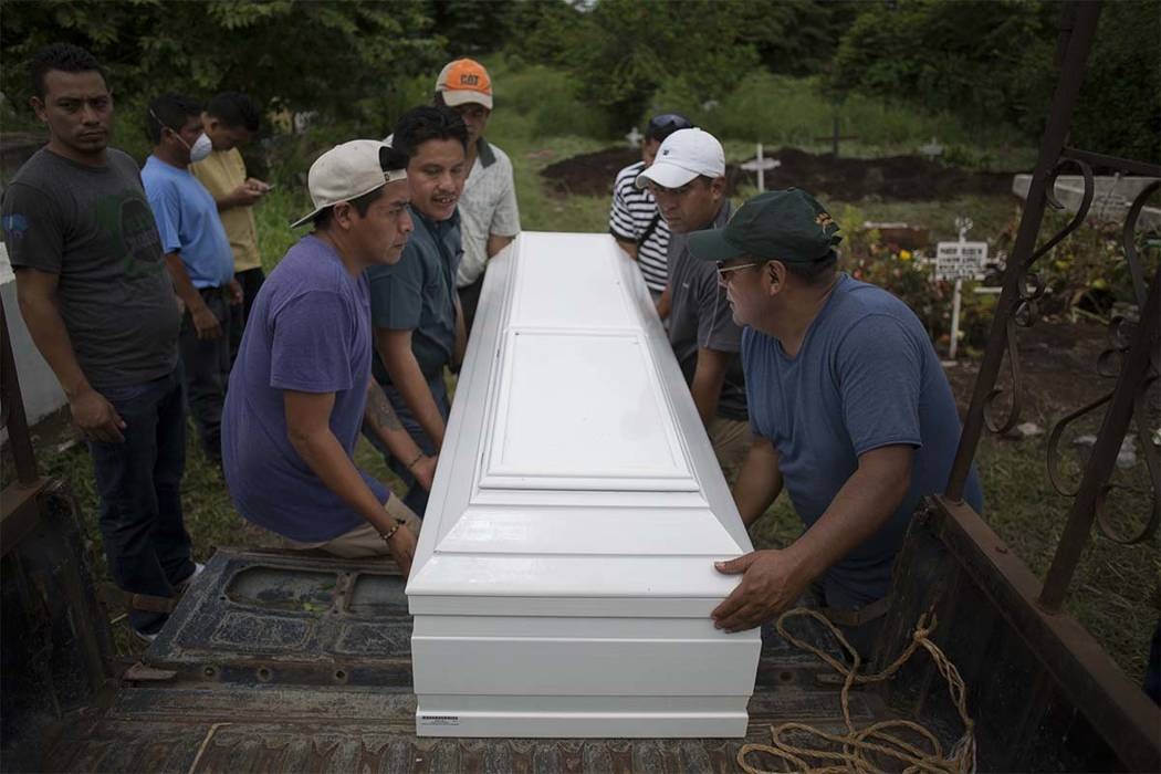 Relatives carry a coffin that contain the remains of Sandra Orizabal Diaz during her burial at the cemetery in Escuintla, Guatemala, Thursday, June 7, 2018. Orizabal's body was interred next to th ...