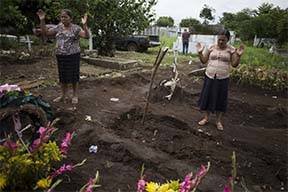 Relatives of Sandra Orizabal Diaz pray during her burial service at a cemetery in Escuintla, Guatemala, Thursday, June 7, 2018. The 37-year-old woman lived in the nearby village of San Miguel Los ...