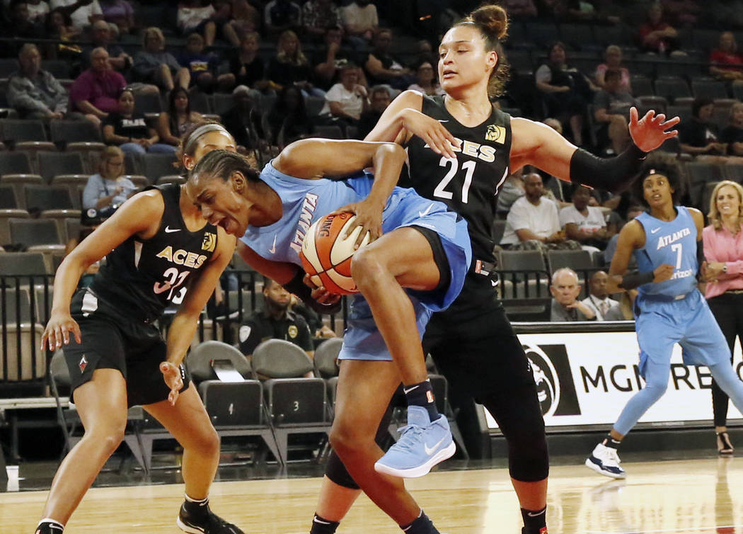Atlanta Dreams's Tiffany Hayes protects the ball from Las Vegas Aces Kayla McBride (21) in the first half of a WNBA basketball game at the Mandalay Bay Event Center in Las Vegas on Friday, June 8, ...