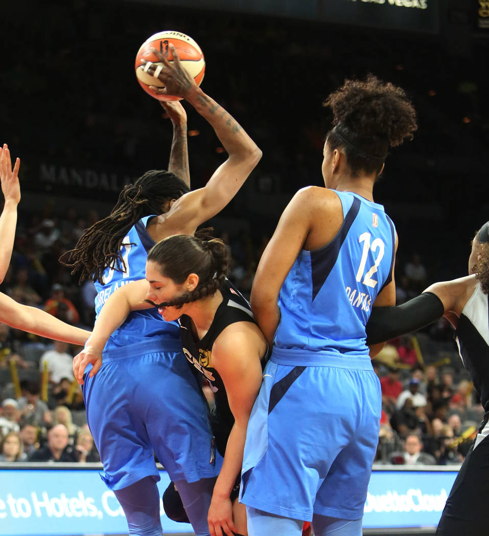Las Vegas Aces center Kelsey Plum, center, looses the ball as she tries to drive past Atlanta Dreams's Damiris Dantas (12) and Jessica Breland (51) in the first half of a WNBA basketball game at t ...
