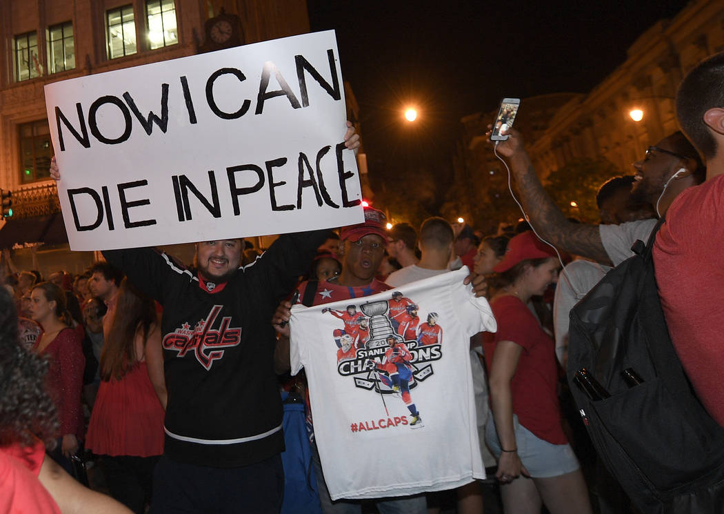 A Washington Capitals fan holds a sign in the streets outside Capital One Arena in Washington after Game 5 of the NHL hockey Stanley Cup Final between the Washington Capitals and the Vegas Golden ...