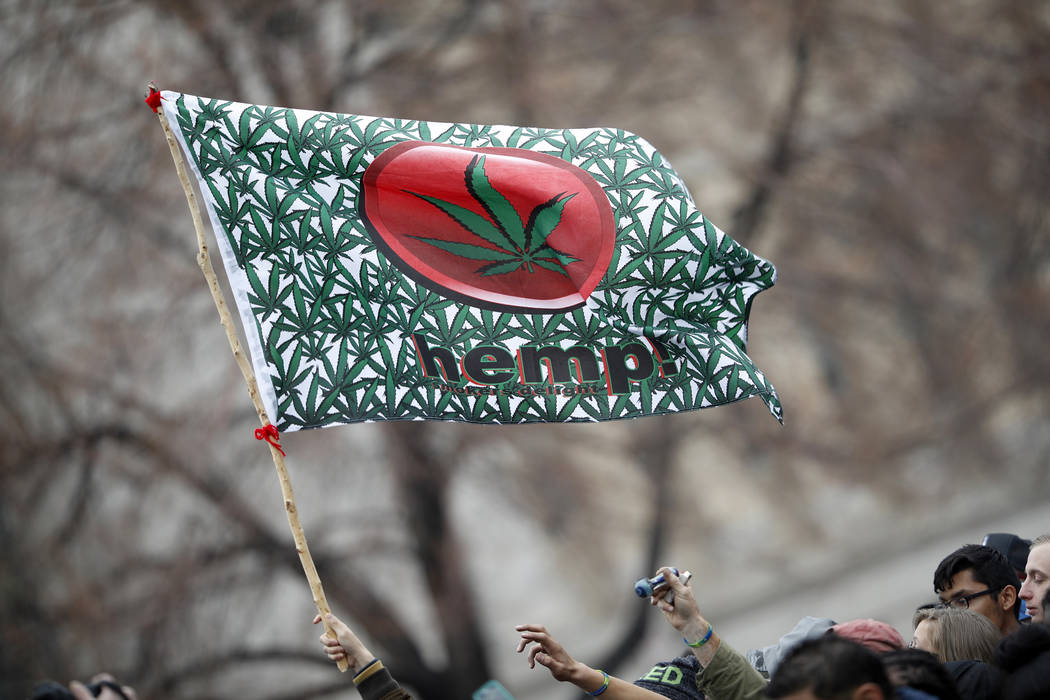 An attendee hoists a flag during the Mile High 420 Festival in Denver in April. (AP Photo/David Zalubowski, File)