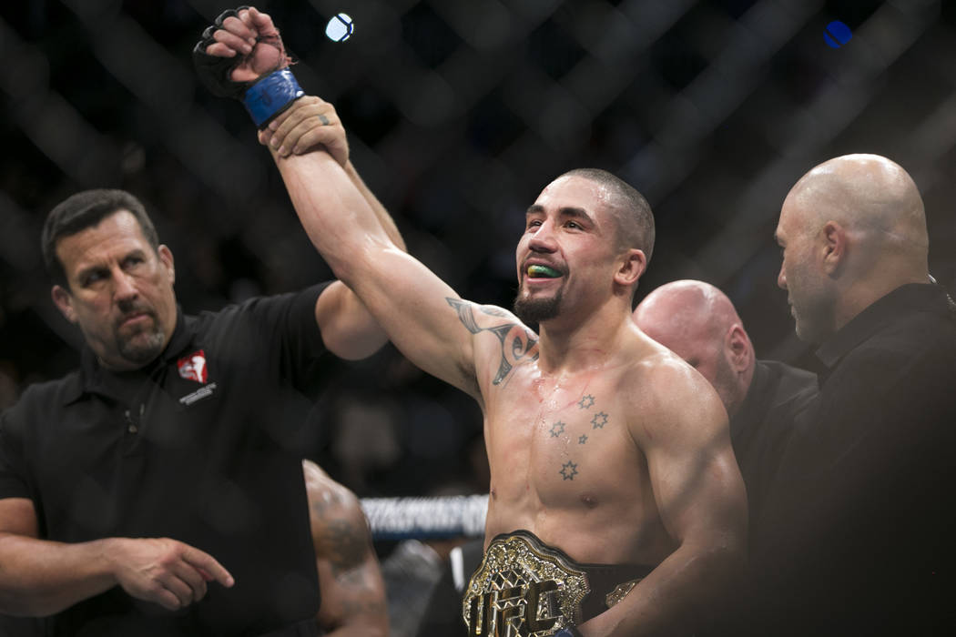 Robert Whittaker, right, is announced the winner by unanimous decision against Yoel Romero in the UFC 213 interim middleweight title bout at T-Mobile Arena in Las Vegas, Saturday, July 8, 2017. Er ...