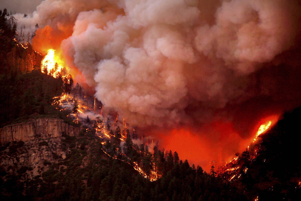In this photo taken Wednesday, June 6, 2018, the 416 Fire burns down Hermosa Cliffs above U.S. Highway 550 on the southeast side of the fire near Hermosa, Colo. (Jerry McBride/Durango Herald via A ...