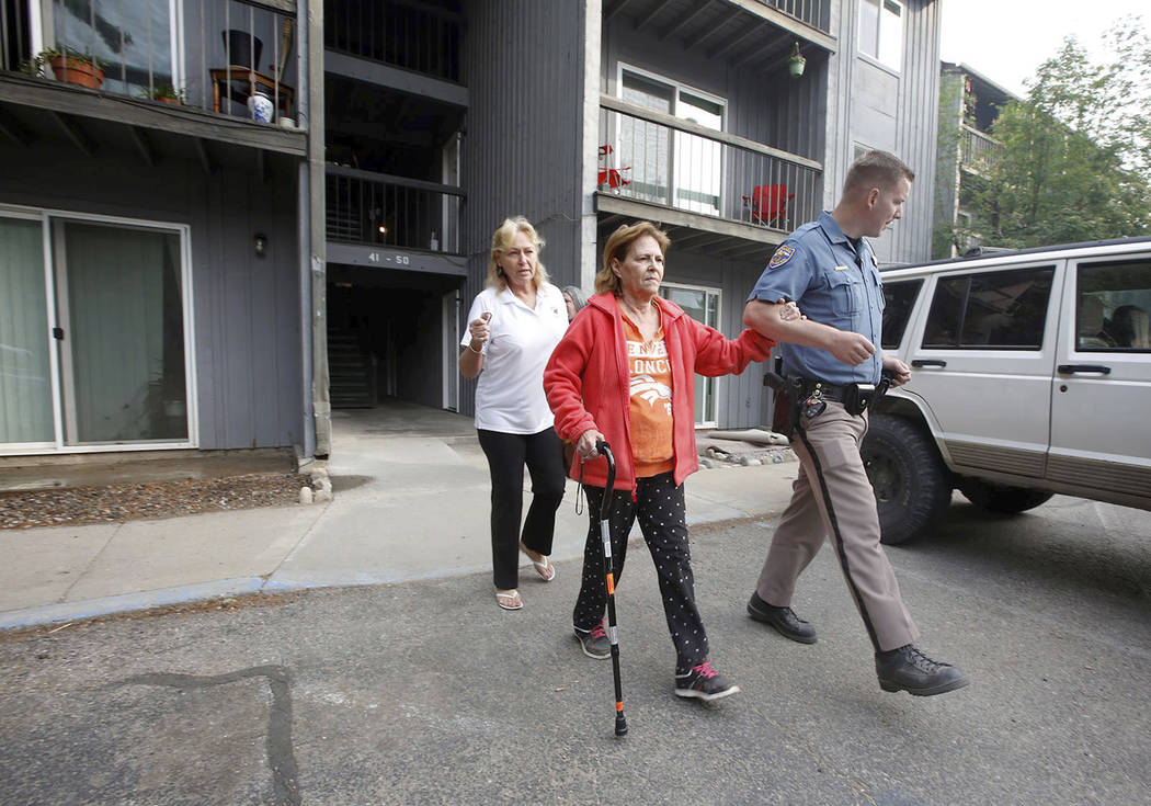 Colorado State Patrol trooper, Brad Spargur, right, escorts a resident as Denakay Hutton, site manager at the Animas Village Apartments, follows on Thursday, June 7, 2018, during the mandatory eva ...