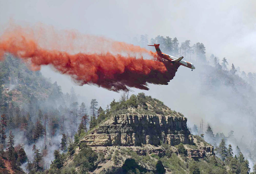 An aircraft makes a fire retardant drop on a wildfire in the mountains and forests near Durango, Colo., Friday, June 8, 2018. (Jerry Day via AP)