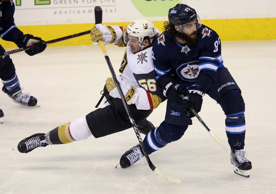 Vegas Golden Knights left wing Erik Haula (56) falls to ice after colliding with Winnipeg Jets center Mathieu Perreault (85) during the third period in Game 2 of an NHL hockey third round playoff ...