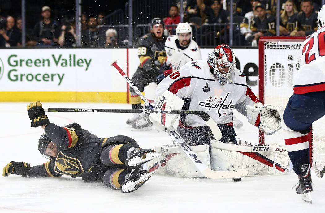 Golden Knights defenseman Colin Miller (6) slips on the ice as Washington Capitals goaltender Braden Holtby (70) defends during the third period of Game 2 of the NHL hockey Stanley Cup Final at th ...