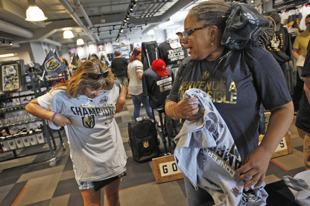 Beverly Marques holds up her Golden Knights western conference championship shirt as Kamala Frazho looks on at the Arsenal retail store at the City National Arena in Las Vegas, Sunday, May 20, 201 ...