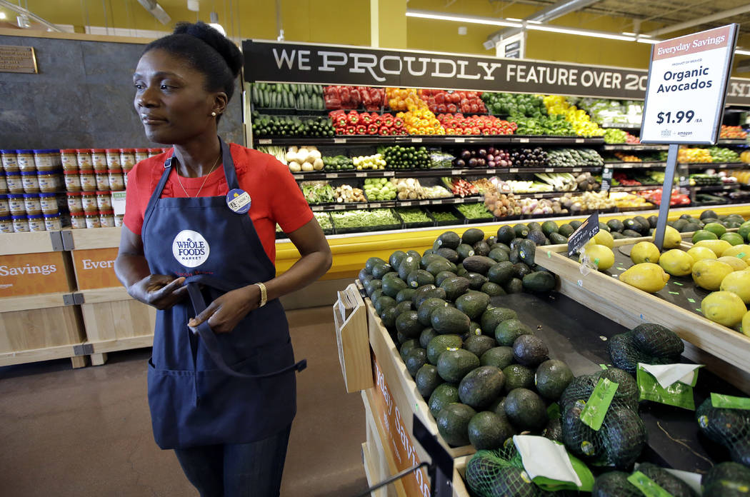 Nadine Vixama, who emigrated from Haiti eight years ago, ties her apron at a Whole Foods where she works in Cambridge, Mass., in May 2018. (AP Photo/Steven Senne)