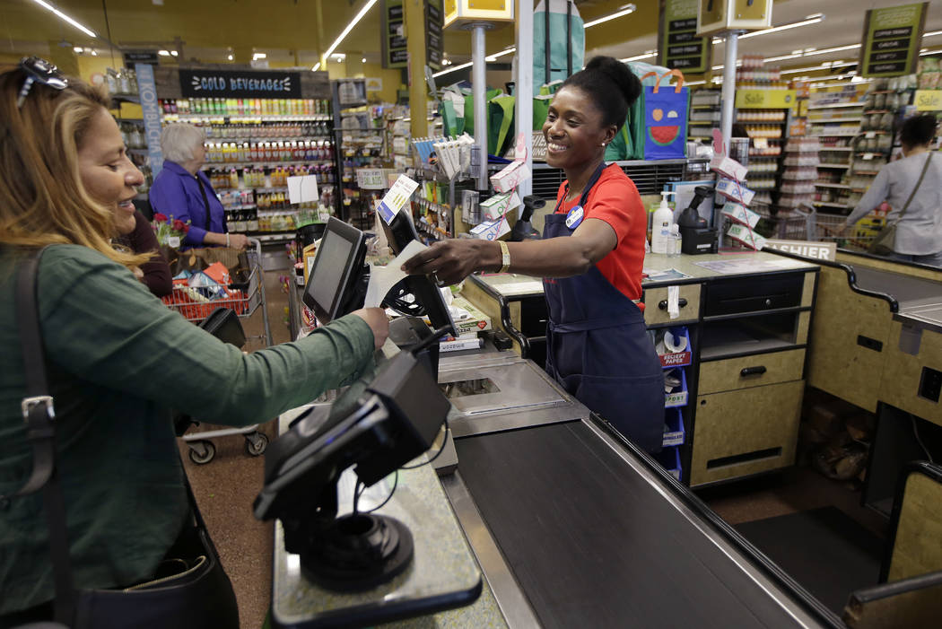 Nadine Vixama, who emigrated from Haiti eight years ago, works as a cashier at a Whole Foods in Cambridge, Mass., in May 2018. (AP Photo/Steven Senne)