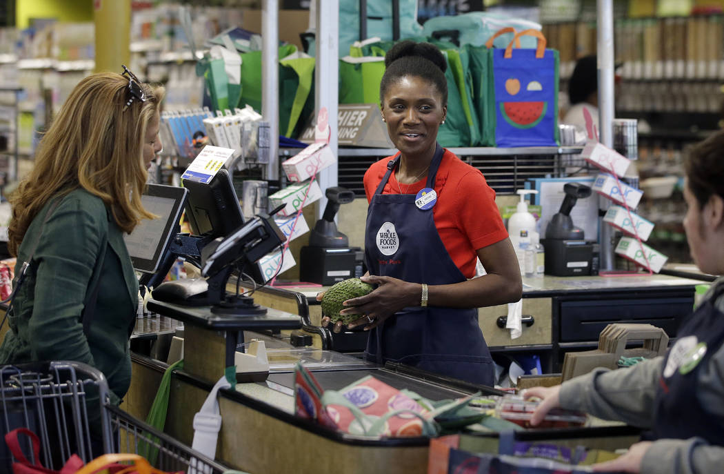 INadine Vixama, who emigrated from Haiti eight years ago, works as a cashier at a Whole Foods in Cambridge, Mass., in May 2018. (AP Photo/Steven Senne)